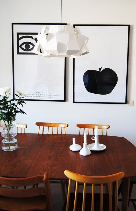 Wooden dining table, fresh flowers, bold art, and daring center lighting.