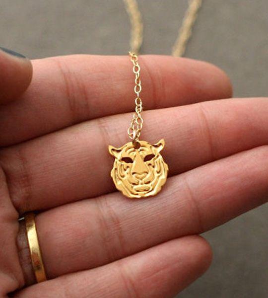 Tiny Tiger halskæde – Guld  Tiny Tiger er et diskret lille tigerhoved i fin guldkæde. Et kraftfuldt symbol på power. Vedhænget er lavet af messing belagt med 24K guld. Den find kæde er forgyldt.