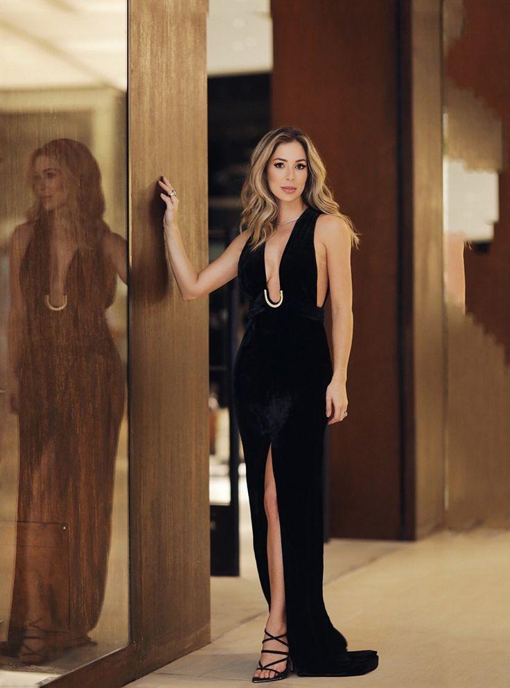 Look para festa de Helena Lunardelli com vestido longo preto de veludo com detalhe metálico e super decote