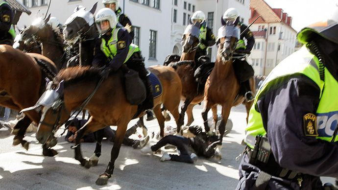 "Police mounted on horses move against counter-demonstrators protesting against an election meeting arranged by the neo-nazi party ""Svenskarn..."