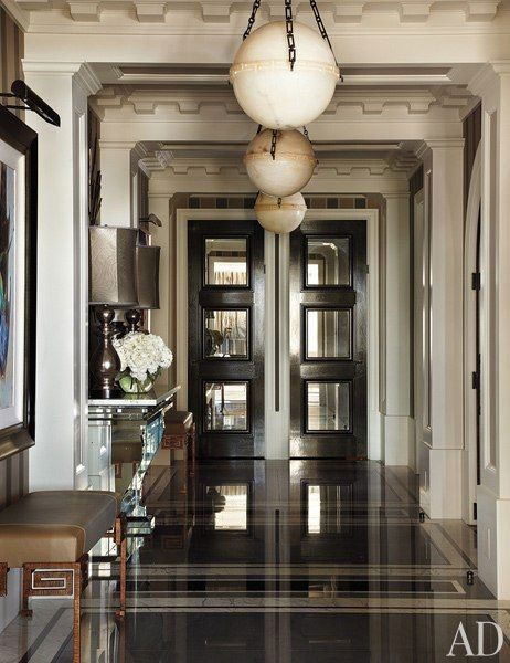 In the entry hall of a Chicago apartment designed by Jean-Louis Deniot, oak doors inset with antiqued mirror lead to the kitchen and private quarters; the pendant lights are by Vaughan, and the leather-and-forged-iron benches were custom made.
