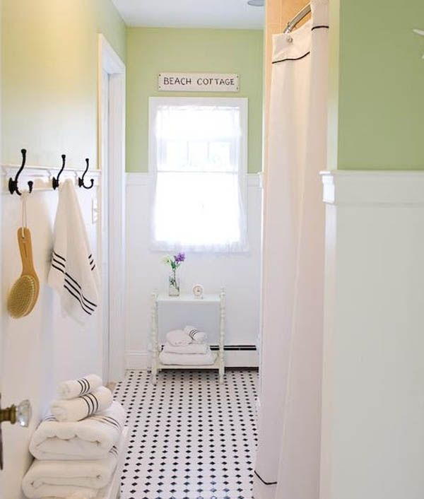 Adorable beach cottage bathroom design with robe & towel hooks, clean white towels, and small purple flower.  So cute!