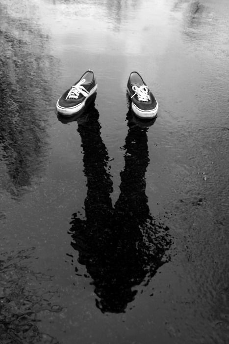 The wet ground imposes a mirror effect to the person standing there, which is interesting since no one is actually standing there.