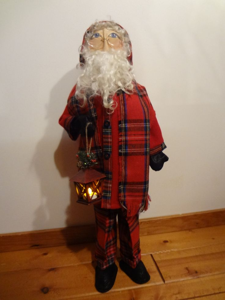 """26"""" Santa wearing glasses w/ red hooded coat & plaid cuffed trousers, matching plaid scarf, leather gloves & shoes, handpainted face, alpaca hair & beard, holding a battery-powered lantern"""