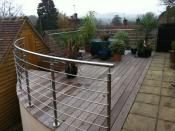 Curved Bar Balustrade, used on a raised decked area. This system allows a curve to be railed using stainless steel posts, handrail and 12mm bar, all shaped to match the balcony curve.