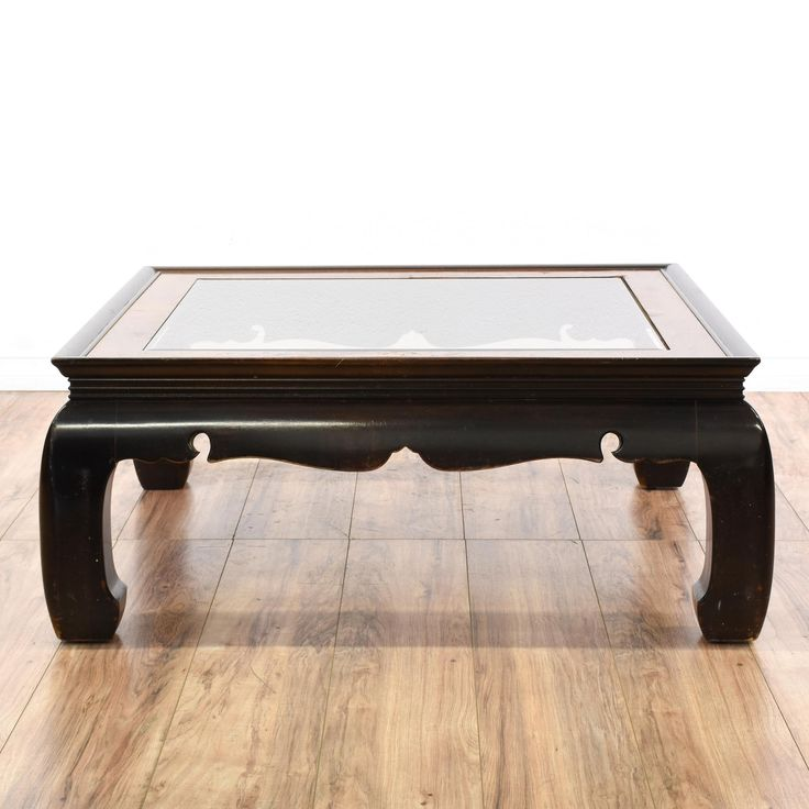This coffee table is featured in a solid wood with a black lacquered finish. This Asian style cocktail table has chow legs, a glass top, and carved trim. Perfect for the living room! #asian #tables #coffeetable #sandiegovintage #vintagefurniture