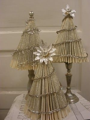 Old books converted into mini christmas trees! fold down diagonally and attach to fan out. Add dollar store or thrifted candlesticks to bottom, voila!