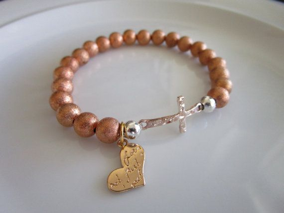 Rose pink gold colored side cross bracelet that will fit most wrists (elastic). The pink rose gold side cross measures 1 inch long by approximately