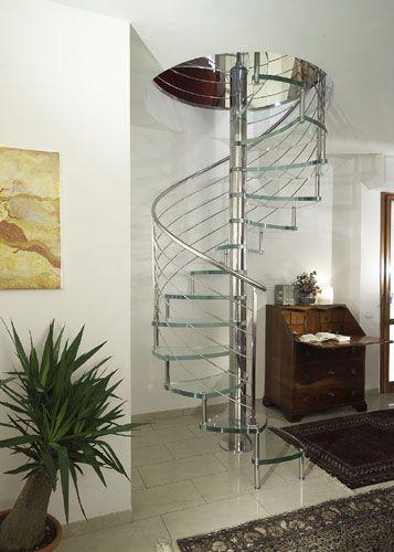 Escalera de caracol con peldaños de cristal estructural extra claro y barandilla con barras horizontales de acero inoxidable.