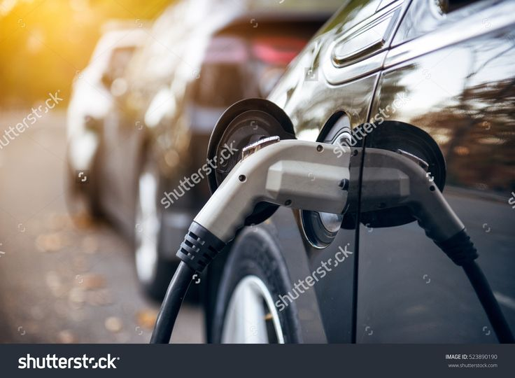 Electric car charging on parking lot with electric car charging station on city street. Electric cars in the row ready for charge. Close up of power supply plugged into an electric car being charged.