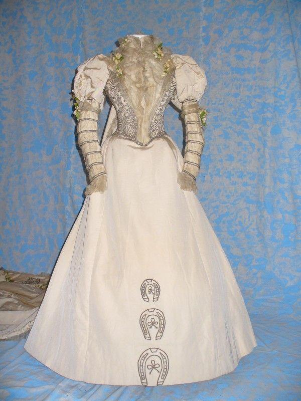 1896: Inghilterra, etichetta: E.FOWLER. Raffinato abito da sposa composto da corpino con lungo strascio e gonna, realizzato in cannellato di seta color avorio e decorato da cordoncino metallico, chiffon di seta, fiori in cera. Stato di conservazione: ottimo.