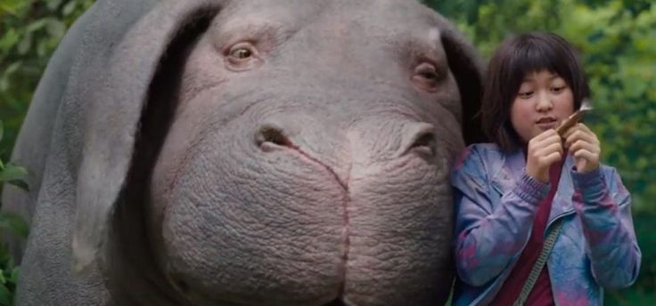 Okja review: Netflixs new sci-fi satire is so sharp it will cut you  Netflix  The science fiction fairy tale Okja begins with a press conference so insane that it's actually believable. In the near future the Mirando corporation is trying to boost its stock prices by announcing a new project: superpigs giant food animals whose poop is environmentally friendly. They'll feed the world without polluting it! That's when things get really weirdand mesmerizing.  Mirando's new president Lucy…