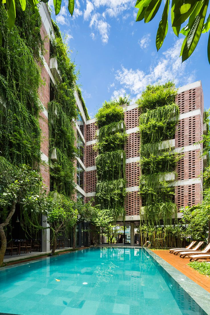 Greenery overflows from concrete planters set into the sandstone walls of this hotel in Hoi An, Vietnam, designed by Vo Trong Nghia