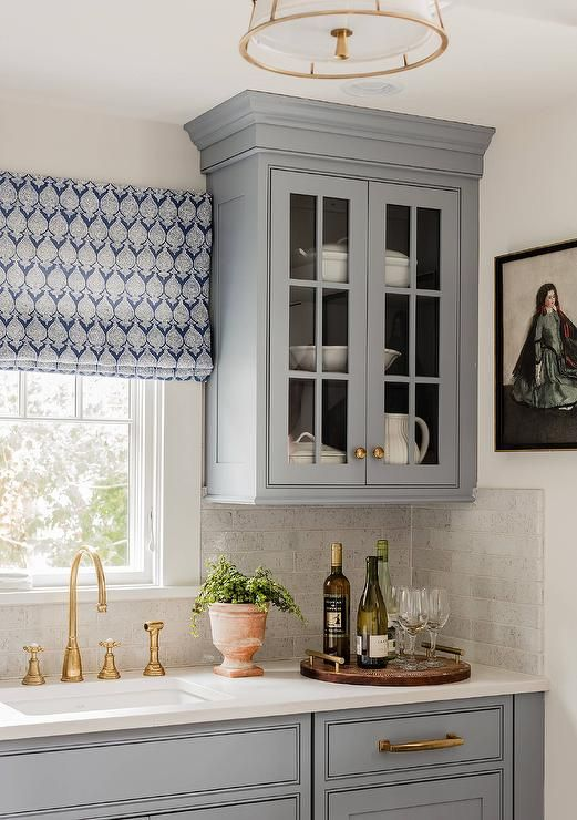A blue gray glass front cabinet adorning antique brass knobs is mounted beside a window dressed in a white and blue roman shade positioned above an antique brass gooseneck faucet paired with a curved undermount sink.