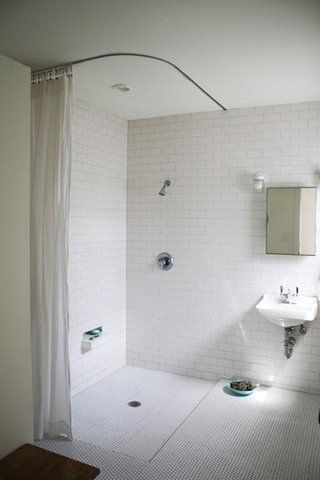 Why spend the money on glass surrounds and all the time it takes to keep them looking good? Change the decor by simply putting up new curtain. Possibly an Ikea curtain track? The recessed ledge is perfect toe-hold for shaving.