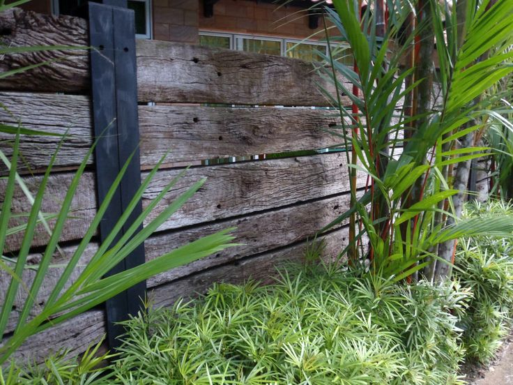 Railway sleeper fence - perfect for the back laneway, maybe the neighbours' side, too. Use some U-shaped purlin as uprights.
