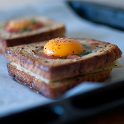 Grilled cheese egg-in-a-hole!   Perfect breakfast with eggs, ham, cheese, tomato, and spring onion.