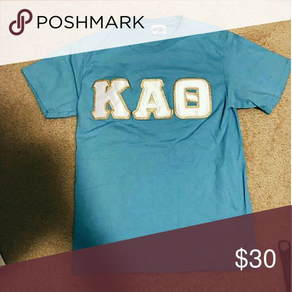 Blue Kappa Alpha Theta Letter T-shirt Announcing a new feature on my shop... sorority apparel (Kappa Alpha Theta)!  This is a classic Greek Letter Shirt in a sky blue color with white sewn-on letters, perfect and versatile for all occasions! Note: Actual brand is Port & Company, American Apparel is just for exposure American Apparel Tops Tees - Short Sleeve