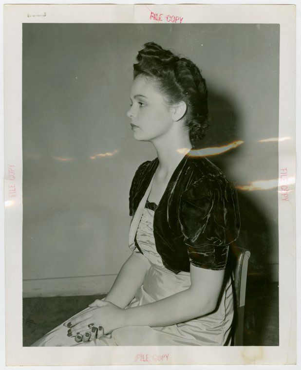"""Hairstyle model Joan McKenna, wearing a """"future Bustle Hair comb - high peaked front and low back with curls."""" Digging her little cropped velvet jacket and dark nails."""
