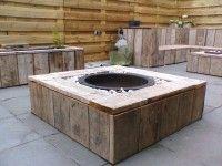 Vuurtafel van steigerhout met een vuurschaal op grindbed in het midden van de tafel.