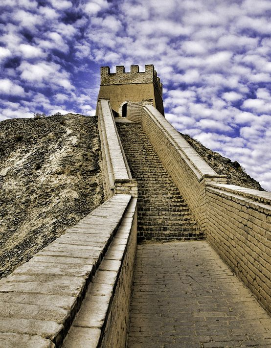 The western end of the Great Wall in China has flanking walls that stretch to the north and south. The northern is rebuilt and takes you up a steep mountain ridge. Here is one of the guard towers near the top where you can enjoy a sweeping view of the Hexi Corridor leading east into central China and the rugged snow capped mountains to the south.