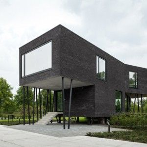 Brick office by Wil-Ma and Wastiau is raised  on angled stilts to protect it from flooding