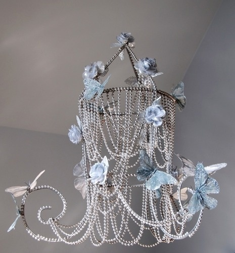 This is so lovely!!! from what I could tell Its made from a Tomato round wire stake (deconstructed & curled) as a base withe costume beads draped all over it and hot glued to it. Fake butterflies& roses with some glitter superglued & hung. ;D Love it!!!