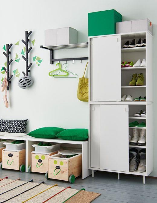 Hall d'entrée avec deux armoires blanches superposées remplies de chaussures rangées sur les tablettes, des boîtes sur roulettes servant de rangement aux chaussures des enfants, glissées sous des bancs, et des supports muraux.