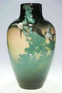 A rare and important Rookwood pottery Black Iris scenic vase done by Kataro Shirayamadani in 1907, five beautifully detailed barn swallows flying through trailing boughs of English ivy. Every detail of the birds is precise, down to individual feathers, tiny feet and eyes. The ivy and swallows contrast wonderfully with the black ground at top and bottom. Marks include the Rookwood logo, the date, shape number 905 B and the incised cipher of the artist.