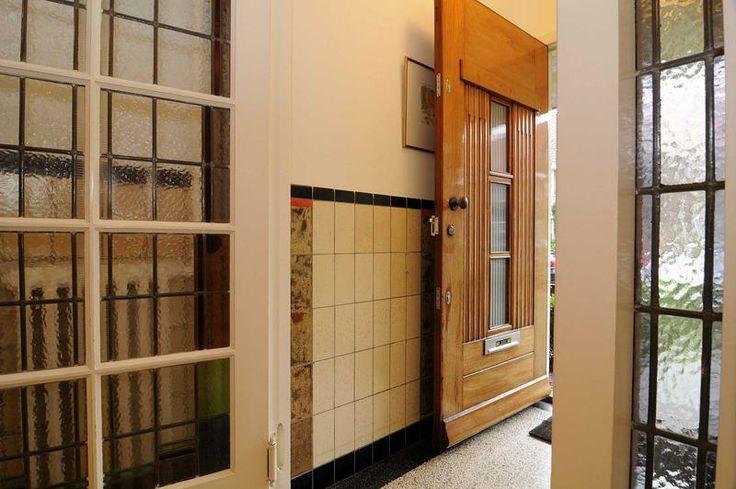 Hal met glas in lood tochtdeuren en tegellambrisering for Taxatie woning