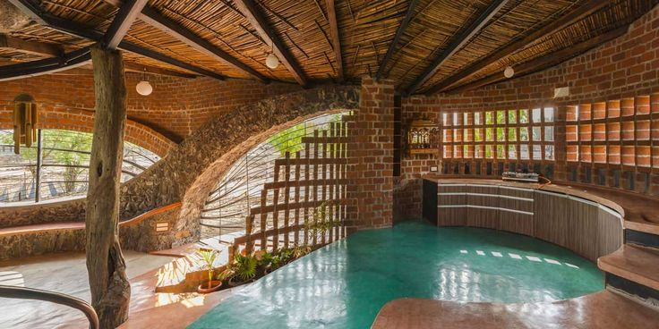 eco friendly, low cost brick house is planned such that each space flows into each other, held by central courtyard, exposed materials giving earthy feel