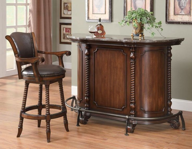 """Home bar unit traditional style marble top curved front warm brown finish wood with decorative front and foot rail.  This set features a stylish design on the front with open shelves and other storage in the back, with a metal foot rail across the front.  Bar unit measures 60"""" x 22.5""""x 42"""" H.  Some assembly required."""