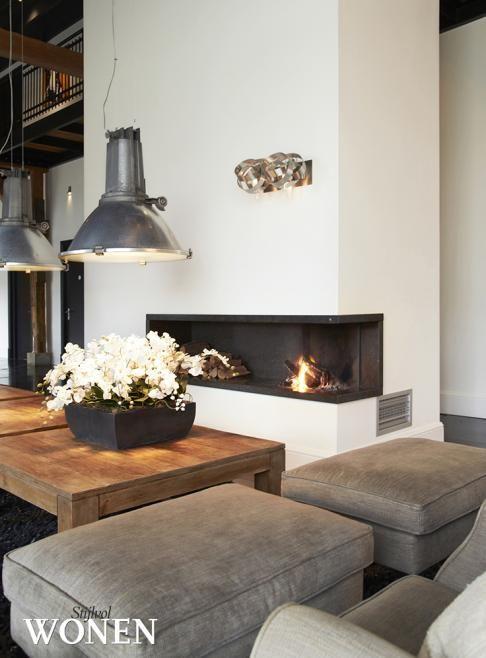 ook leuk, industriele lamp boven salontafel. Met sfeerhaard in een nisje.