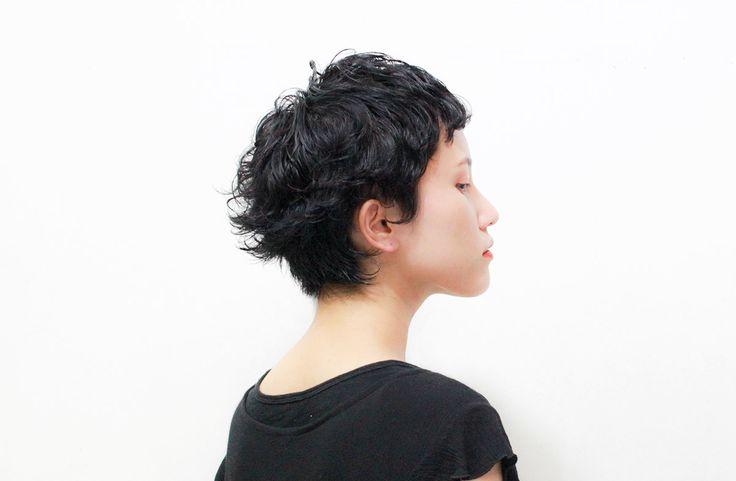 潔くかっこいい黒髪ショートに  クールな外人風パーマを施しつつ、アウトラインから耳裏にかけて作った外ハネとバングの短さで可愛さもほどよくプラスしたスタイル。  スタイリングは湿った髪にまんべんなくムースをつけて形を作りながら少しドライヤーで水分をとばす。  ハイトーンもオススメですが肌の白さ…