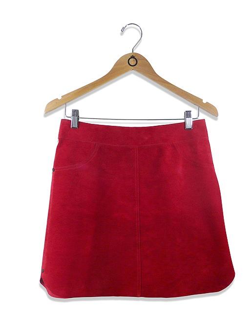 Saia boxer em camurça vermelha com rebites pretos nas laterais. Bolsos falsos na frente. A saia abre atrás com zíper invisível nas costas. R$203.90