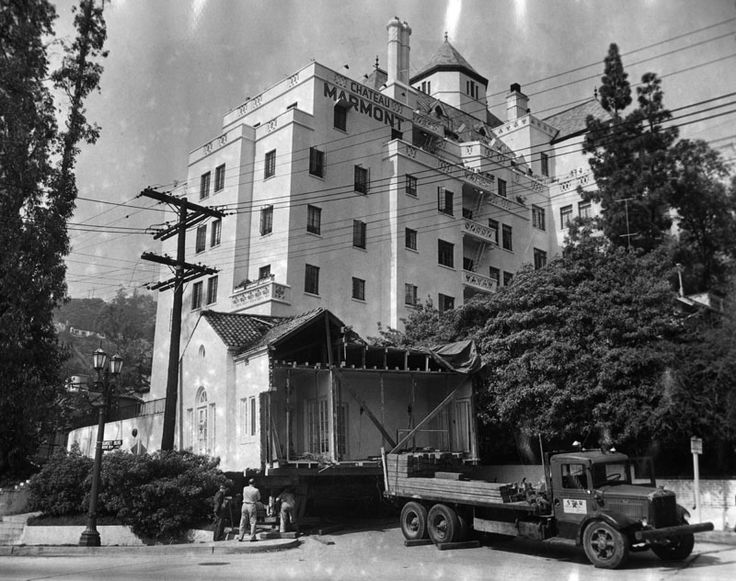 A house being moved down Sunset to West Hollywood passes by the Chateau Marmont, 1950.