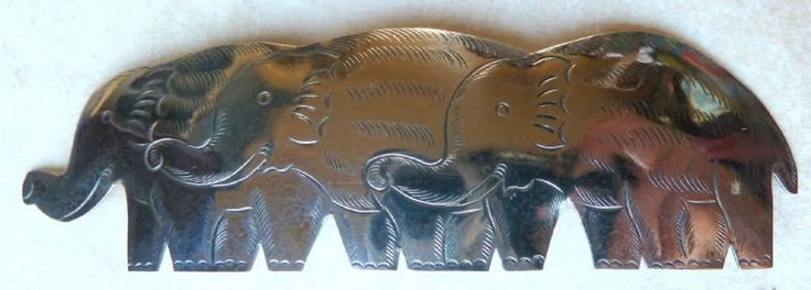 This is a large curved vintage elephant brooch The brooch design is a trio of elephants traveling together The elephants are identical in size and