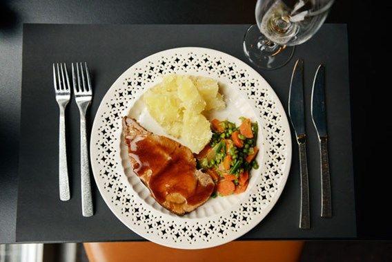 Varkensgebraad met erwtjes en wortelen, aardappelen en bruine jus