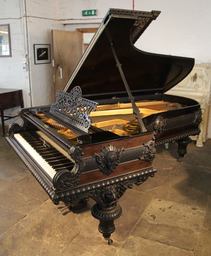 An 1883, Neoclassical style, Bechstein Model C grand piano for sale with a Pear and Ebony case at Besbrode Pianos. Entire cabinet features ornately carved, Neoclasssical elements. Female figureheads surround the case, lions heads sit at the top of each leg. Arabesques, rosettes, fleur de lys, beading and anthemions pull the design together. The piano left the Bechstein factory in 1884 and was sent to acabinet makers in Munich where the decoration was added post production.