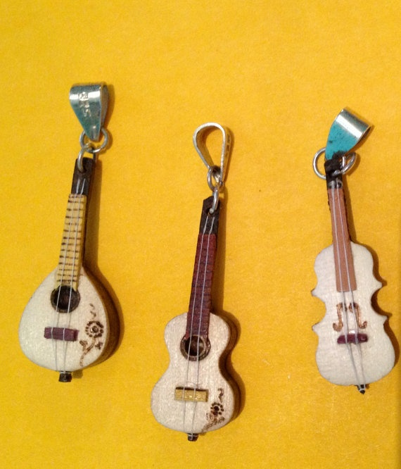 Music to your ears! Mandolin and Guitar pendants. Each guitar pendant is intricately carved from 3 different types of tropical wood found throughout Latin America while each mandolin pendant is carved from 4 different types of wood.