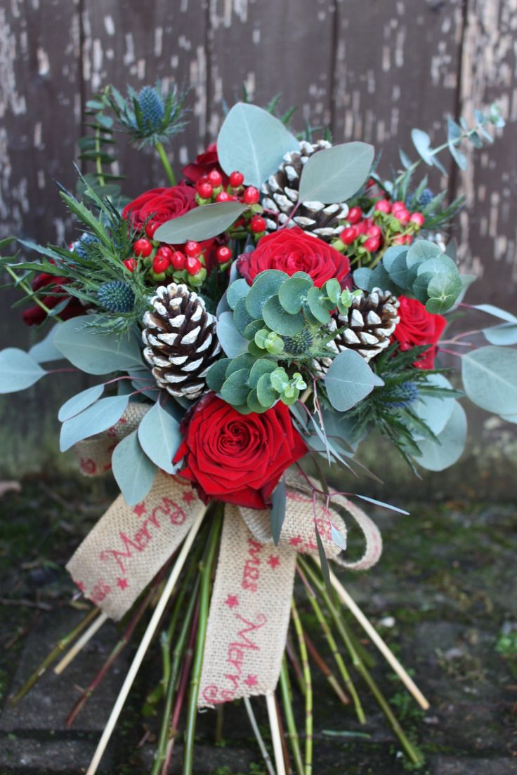 Sumptuous Christmas bouquet filled with red Naomi Roses, blue Thistle, Hypericum and pine cones