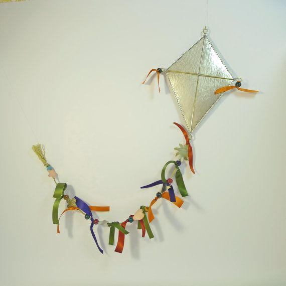 This uniquely hand-crafted wall hanging metal kite is made of white silver also known as german silver or alpacca. It is decorated with a playful tail made with a variety of hand-cut metal elements. A sun, a little bird, a flower, a heart, and a star cheerfully hanging between satin ribbons, and colourful clay beads. A unique and original gift for a kids room that stimulates imagination and a modern ornament for home decor.  On its back surface is soldered a small hook for easy hanging…