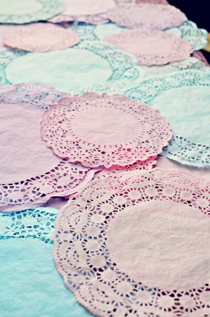 Dyed doilies Tutorial -  Submerge doily into food coloring. Leave in for a few seconds. Carefully remove the doily. The best method was to lift it from the solid paper center. Place on a paper towel. Blot with another paper towel. Let dry.