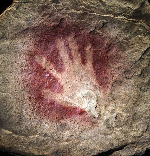 """A 30,000 year old hand print from Chauvet Cave in France. They think the artist put red ochre """"paint"""" in her mouth, placed her hand on the rock, then spat it out in a spray to create this negative image. Most of the handprints seem to be from an adolescent or possibly a female."""