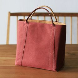 < コンセプト >日本製の帆布とイタリア製バケッタレザーを使用し丁寧な製法で上品な雰囲気に仕上げたシンプルな帆布のトートバッグ< 特 徴 >●小さく見えつつ収納力のある上すぼまりフォルム●クッション素材を内張りすることでハンドバッグのように自立する構造●握り心地の良い革巻きハンドル< こだわり >●ハンドバッグの製法(ヘリ返しなど)を取り入れた上品で丁寧な縫製●革の端面は丁寧なコバ塗り仕上げ●使うほどに味わいの増すイタリア製バケッタレザー使用< 収 納 >●クッション内張りで壊れやすいもの(スマホやカメラなど)を入れても安心●A5ノート/スマートフォン/財布/ミラーレスカメラ等を収納可能●スマートフォンや定期入れを収納できる内ポケット< 寸 法 >本体サイズ:縦25cm 横25cm 奥行き15cm持ち手:26cm< 素 材 >本 体:パラフィン加工10号コットンキャンバス(日本製)(色:レンガ)裏 地:コットンツイル(日本製)(色:ブラウン)皮 革:タンニン鞣し牛革(イタリア製)(色:ヌメ)< その他…