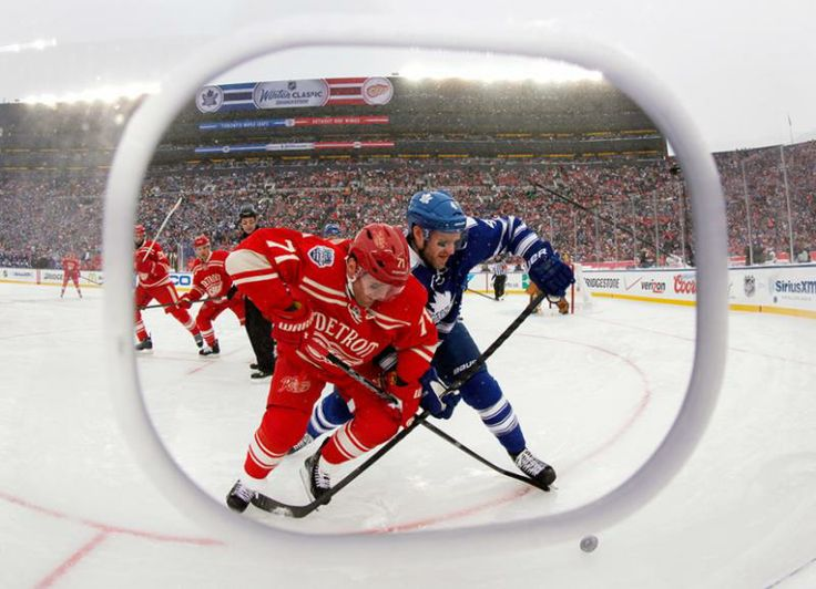 Framed by a cutout in the safety glass, Red Wings right winger Daniel Cleary (71) and Maple Leafs defenseman Cody Franson (4) battle for the puck during the third period. (Paul Sancya/AP)