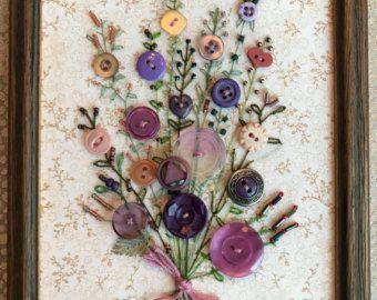 Jai cousu à la main chaque bouton et les tiges sur le tissu de brodées à la main. Perles de rocaille sont cousues aux sommets des tiges comme les bourgeons floraux. Cette douce image décorative est encadrée dans un barnwood rustique cadre 6 « x 7 » avec un cintre en dents de scie sur le dos. Il sagit dun dun bon morceau. Le tissu a un tirage qui ressemble à une vieille carte. Il y a 2 boutons de pot de fleur qui sont de couleurs différentes.
