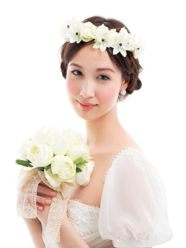 ゆるい三つ編みのまとめ髪にのせた白の花冠が、花嫁の清楚さと愛らしさを引き立てて。バレリーナのように麗しく、老若男女問わず愛される、人気のスタ...