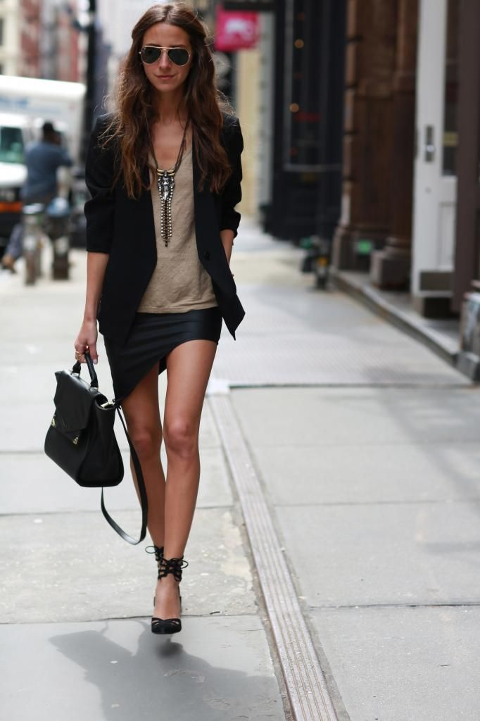 Black blazer, statement necklace, beige top, asymmetrical skirt, black heels, black bag