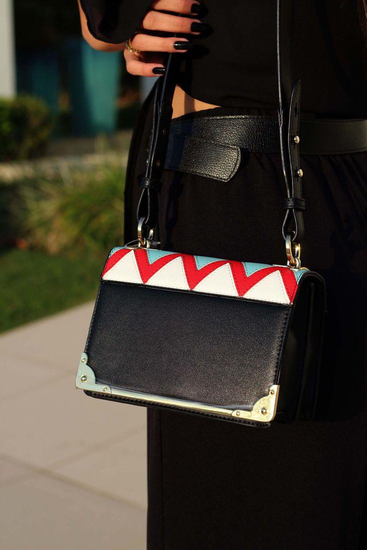 Bolsa em couro sintético preto com a parte de cima em zigue zague branco, vermelho e azul, alça e fechos dourados